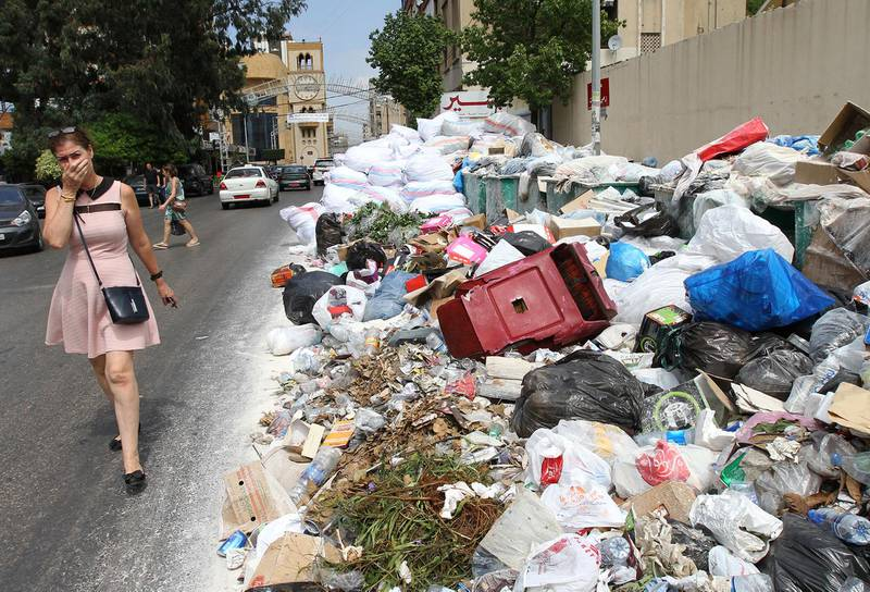 A woman holds her breath as she walks near a temporary garbage dump in the neighbourhood of Jdeideh, northeast of the Lebanese capital Beirut on September 1, 2016. - Lebanon has been going through a garbage crisis caused by the closure of its main landfill more than a year ago. (Photo by ANWAR AMRO / AFP)