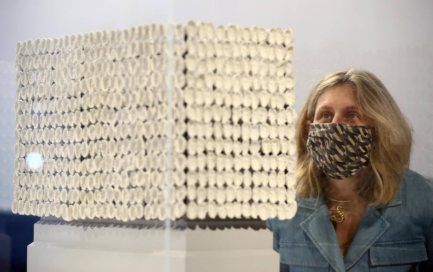 """A gallery assistant poses as she looks at """"Improntas (Imprint)"""" by Teresa Margolles, one of six artworks shortlisted as the next design for the Fourth Plinth at Trafalgar Square, on display inside the National Gallery in London, Britain, May 24, 2021. REUTERS/Hannah McKay"""