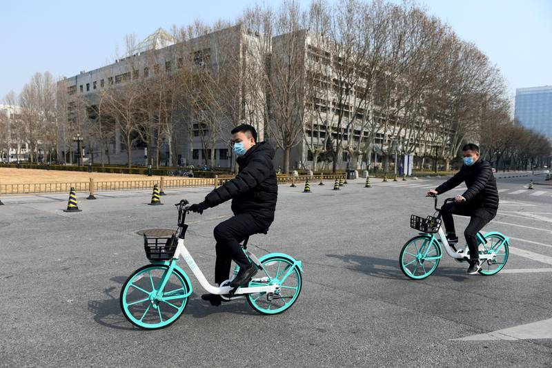 Two men wear face masks as a preventive measure against the COVID-19 coronavirus as they ride bikes in the empty grounds of Tsinghua University in Beijing on February 28, 2020. - The university, along with others in Beijing, has postponed the official start of the new semester due to the coronavirus outbreak, but has instead offered online courses. China reported 44 more deaths from the novel coronavirus epidemic on February 28 and 327 fresh cases, the lowest daily figure for new infections in more than a month. (Photo by GREG BAKER / AFP)