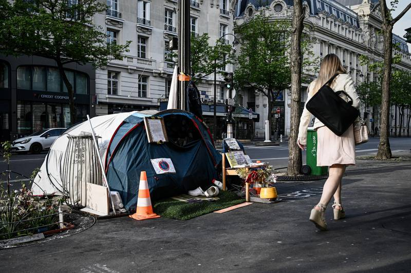 A woman walks past the tent of a homeless set up on the pavement in Paris on April 16, 2020 on the 31th day of a lockdown in France aimed at curbing the spread of the COVID-19 pandemic, caused by the novel coronavirus. (Photo by Philippe LOPEZ / AFP)