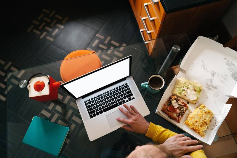 A middle-aged man sitting in the kitchen at the glass table with laptop in headphones and holding pizza and coffee. View from above. Concepts of working at home during quarantine during a coronavirus pandemic. Getty Images