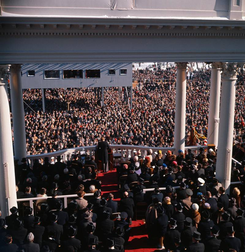 Back view of President John F. Kennedy and crowd as he gives inaugural speech.