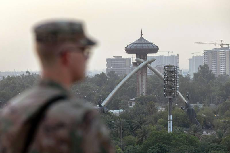 BAGHDAD, IRAQ - MAY 30: A U.S. Army soldier looks onto Baghdad and the Saddam-era Crossed Sabers monument from the International Zone on May 30, 2021 in Baghdad, Iraq. Coalition forces based in Baghdad's International Zone are part of the U.S.-led Military Advisor Group of 13 nations supporting the Iraqi Security Forces. The United States currently maintains 2,500 military personnel in Iraq as part of Operation Inherent Resolve. Alpha Company 769th brigade Engineer Battalion, Louisiana National Guard is providing force protection at the base.   John Moore/Getty Images/AFP == FOR NEWSPAPERS, INTERNET, TELCOS & TELEVISION USE ONLY ==