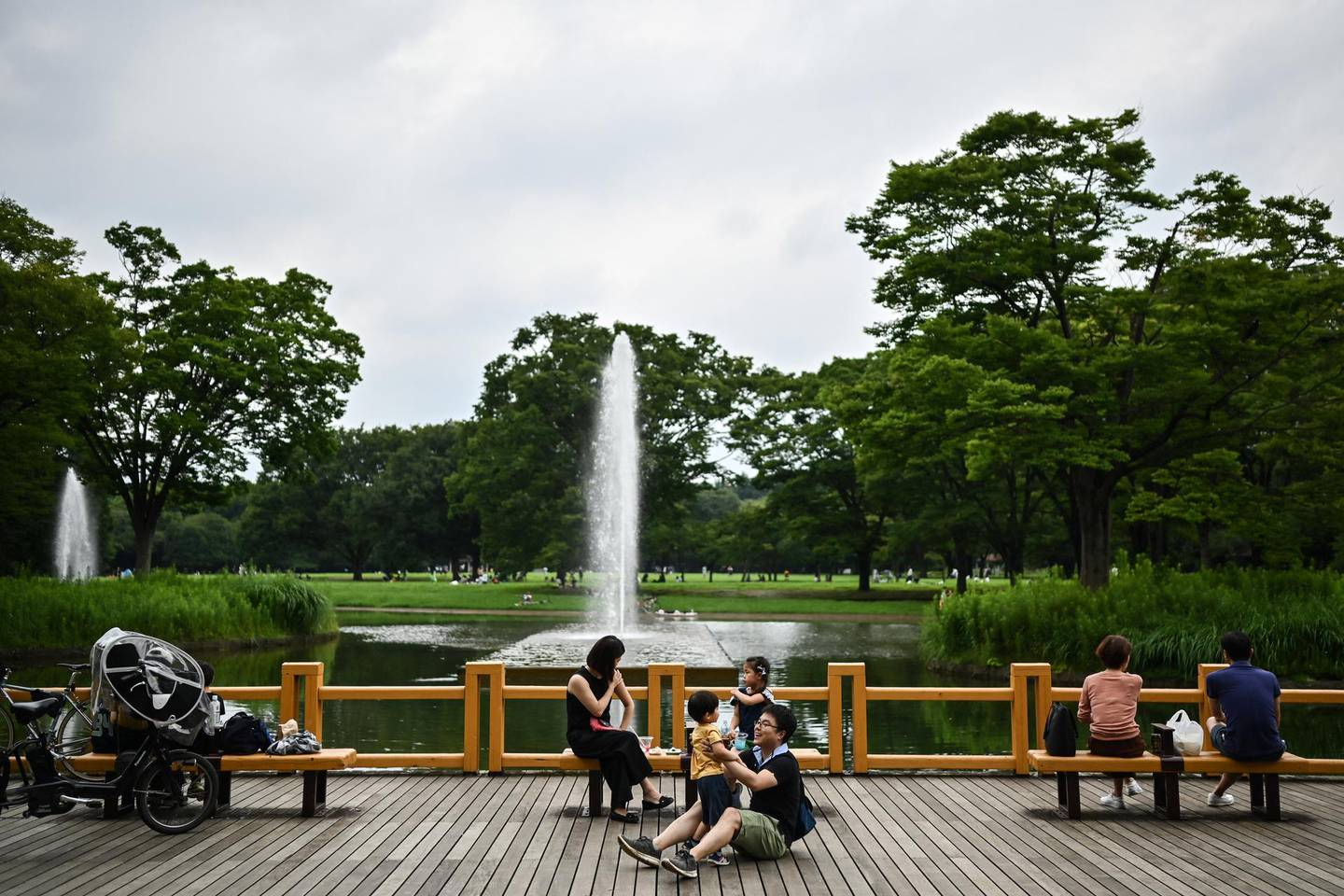 A woman and a child interact at Yoyogi Park in Tokyo on July 24, 2020. (Photo by Charly TRIBALLEAU / AFP)