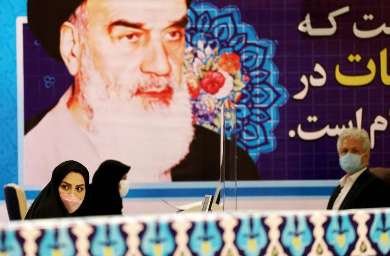 Staff members sit under a portrait of the Islamic republic's late revolutionary leader Ayatollah Ruhollah Khomeini, while registering candidates for Iran's presidential elections at the Interior Ministry in Tehran on May 11, 2021. Registration at the interior ministry to contest the poll runs from today to May 15, with names to be handed to the conservative-dominated Guardian Council for vetting before being allowed to run. / AFP / ATTA KENARE