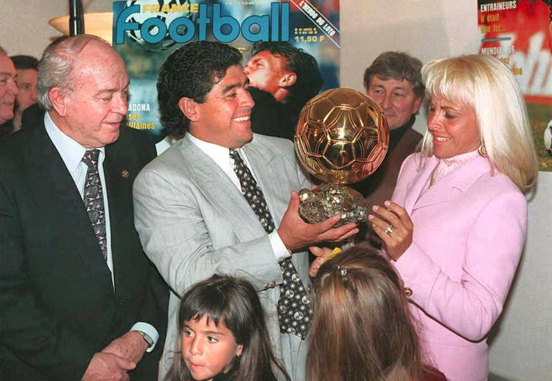 """Argentinian soccer star Diego Maradona (C) hands the honorary """"Ballon d'Or"""" (Golden Ball) award he received 03 January to his wife Claudia, as former soccer great Alfredo Di Stefano (L) looks on. In the foreground are Maradona's daughters Giannina (L) and Dalma (R). (Photo by PATRICK KOVARIK / AFP)"""