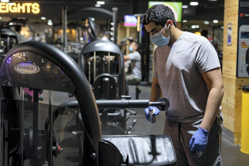 Dubai, United Arab Emirates - Reporter: Kelly Clark: News. A man cleans the equipment after he uses it at GymNation in Al Quoz as gyms across Dubai start to open. Wednesday, May 27th, 2020. Dubai. Chris Whiteoak / The National