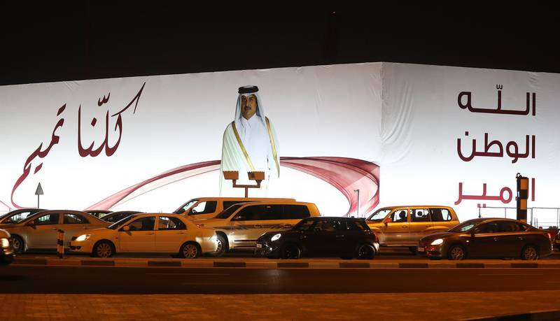 """(FILES) In this file photo taken on June 11, 2017 A general view taken on June 11, 2017 shows a portrait of Qatar's Emir Sheikh Tamim bin Hamad Al-Thani and text reading in Arabic: """"We are all Tamim"""" on a billboard outside the Qatar Sports club in Doha after the diplomatic crisis surrounding Qatar and the other Gulf countries spilled from social media to more traditional forms of media -- all the way back to billboards.  The year-old acrimonious dispute between Qatar and its neighbours is forging a """"new"""" Gulf, potentially transforming what was a stable region of the Arab world, experts warn.  / AFP / Karim JAAFAR"""