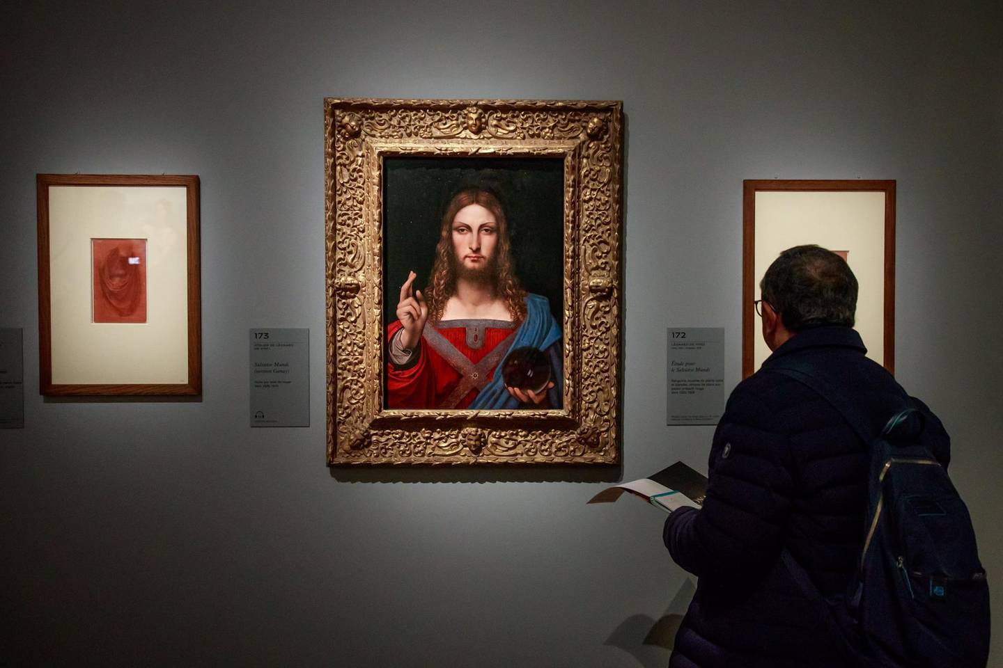 epa07940158 A visitor looks at the painting entitled 'Salvator Mundi' by Italian Renaissance artist Leonardo Da Vinci's workshop during an exhibition at the Louvre Museum in Paris, France, 22 October 2019. The exhbition running from 24 October 2019 to 24 February 2020 marks the 500th anniversary of Da Vinci's death.  EPA/CHRISTOPHE PETIT TESSON