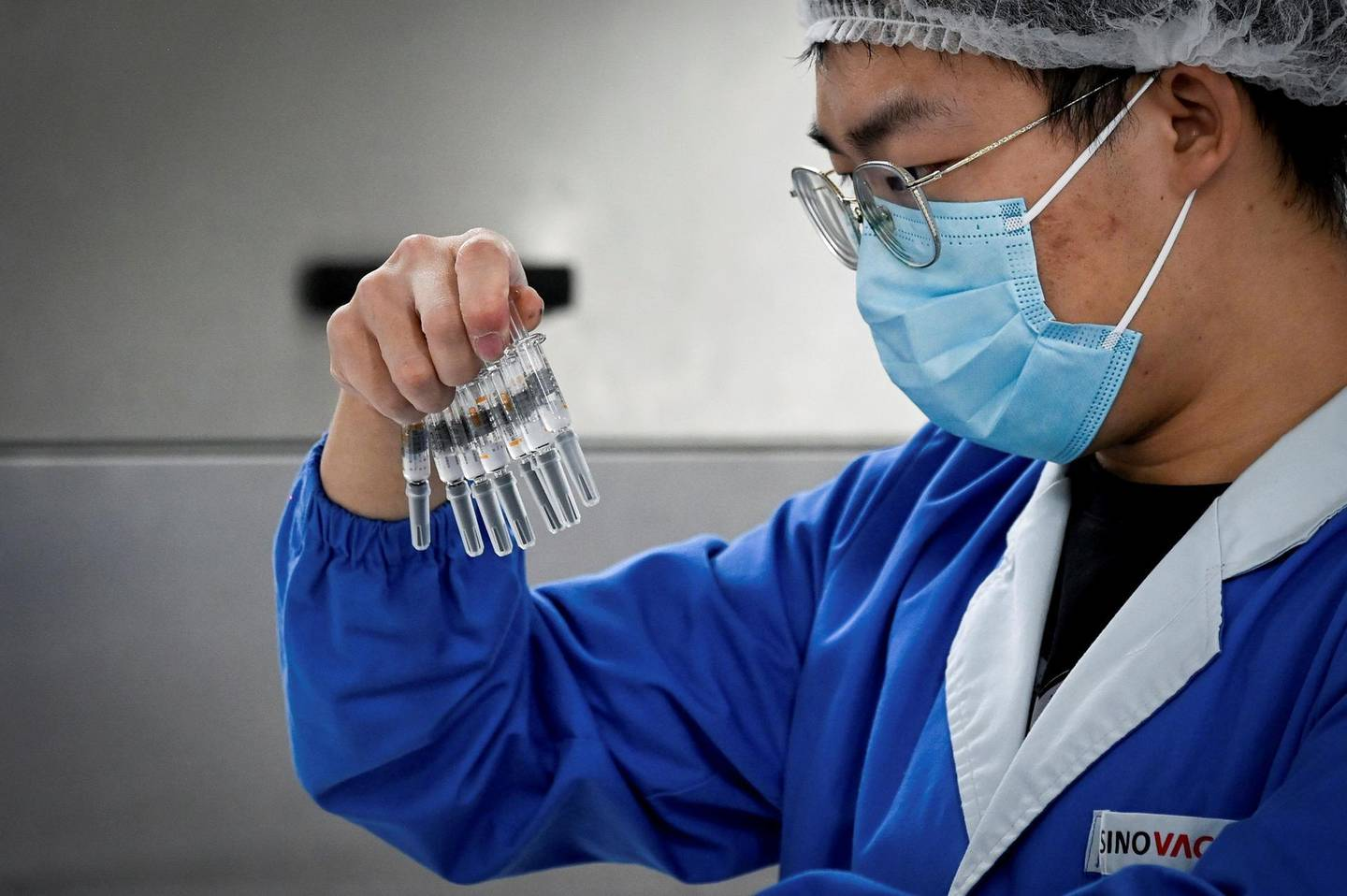 (FILES) This file photo taken on September 24, 2020 shows a staff member checking vaccines during a media tour of a new factory built to produce a COVID-19 coronavirus vaccine at Sinovac, one of 11 Chinese companies approved to carry out clinical trials of potential coronavirus vaccines, in Beijing.  China has launched a global charm offensive promising poorer nations priority access to its coronavirus vaccines in a bid to repair an international image tarnished by the pandemic. -   / AFP / WANG Zhao