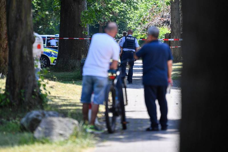 17 June 2021, North Rhine-Westphalia, Espelkamp: Two men watch as police officers walk along a path. According to the Bielefeld police, two people have been shot in Espelkamp. The perpetrator is still on the run, a police spokesman told the German Press Agency on Thursday. Important: For editorial news reporting purposes only. Not used for commercial or marketing purposes without prior written approval of UEFA. Images must appear as still images and must not emulate match action video footage. Photographs published in online publications (whether via the Internet or otherwise) shall have an interval of at least 20 seconds between the posting. Photo: Lino Mirgeler/dpa (Photo by Lino Mirgeler/picture alliance via Getty Images)