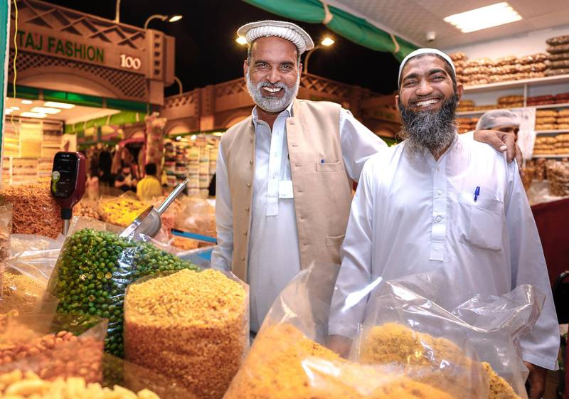 Abu Dhabi, United Arab Emirates, January 5, 2020. Photo essay of Global Village. -- Cousins and partners of Karachi Nimko, a snack stall which sells peanuts, peas and other finger snacks. Both from Islamabad, Pakistan.Malik Abdul Rehman, 49, right,  and Mohammad Bashir, 50.  They have been operating the shop for eight years now.Victor Besa / The NationalSection:  WKReporter:  Katy Gillett