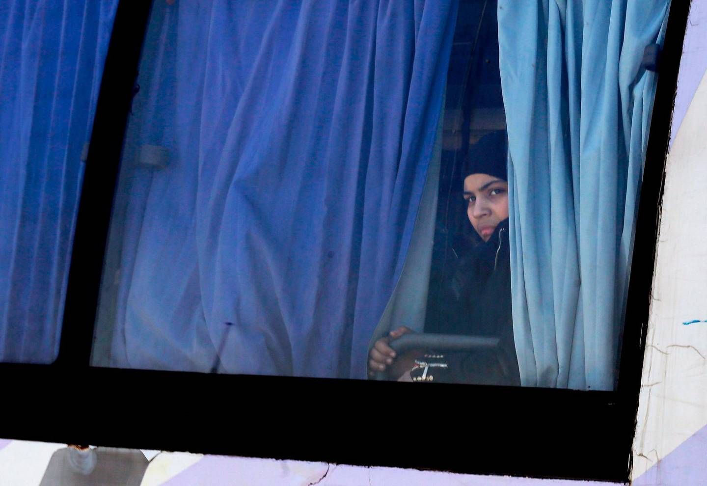 A Syrian woman looks out of the window of a bus as Syrian civilians and rebel fighters evacuated from Eastern Ghouta arrive in a government-held area at the entrance of Harasta on the outskirts of the capital Damascus, on March 26, 2018.  More than 2,500 Syrian rebels and civilians prepared to leave Eastern Ghouta on March 26 after the largest exodus yet from the opposition enclave, as talks stalled over the final pocket of resistance. / AFP PHOTO / LOUAI BESHARA