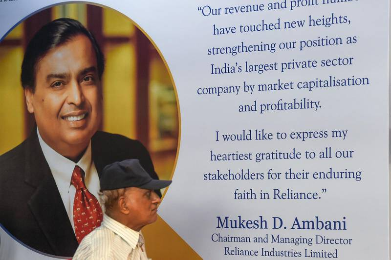 A shareholder walks past a poster of India's richest man and oil-to-telecom conglomerate Reliance Industries chairman Mukesh Ambani at the company's 42nd AGM in Mumbai on August 12, 2019.   / AFP / Indranil MUKHERJEE