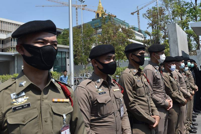 Police wearing facemasks, amid concerns over the spread of the COVID-19 novel coronavirus, stand guard outside the parliament building, currently under construction, as people take part in a demonstration calling for the creation of a new constitution in Bangkok on March 13, 2020. / AFP / Romeo GACAD