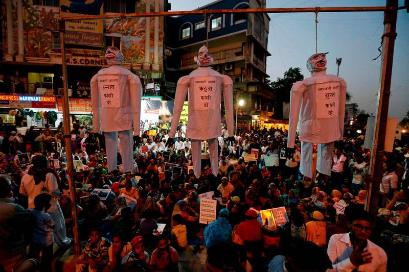 """FILE - In this April 17, 2018 file photo, effigies hang on nooses with the words, from left to right, """"hang the guilty in the Unnao rape case,"""" """"Hang the guilty in the Kathua rape case,"""" and """"hang the guilty in the Surat rape case,"""" referring to recent cases and allegations of rape, during a protest in Ahmadabad, India. India's government has decided to prescribe the death penalty for people convicted of raping girls under the age of 12 to combat an increase in crimes against women. The Press Trust of India news agency reported Saturday, April 21, 2018, that the ordinance is being sent to the president for approval. It will require the approval of Parliament within six months in order the become law. (AP Photo/Ajit Solanki, File)"""