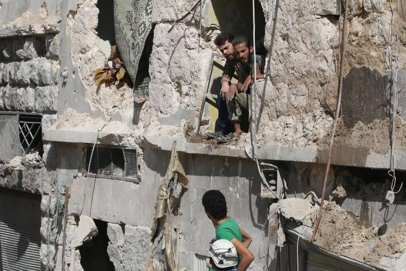 Men inspect a site damaged after an airstrike in the besieged rebel-held al-Qaterji neighbourhood of Aleppo, Syria October 11, 2016. REUTERS/Abdalrhman Ismail