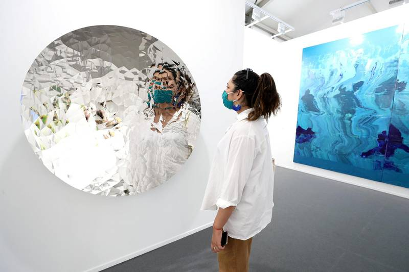Dubai, United Arab Emirates - Reporter: Alexandra Chaves. Arts and Lifestyle. A visitor looks at a piece by Anish Kapoor called Random Triangle Mirror. Art Dubai 2021 opens at the DIFC. Tuesday, March 30th, 2021. Dubai. Chris Whiteoak / The National