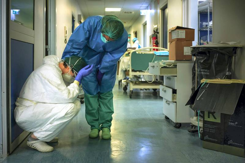 """A nurse wearing protective mask and gear comforts another as they change shifts on March 13, 2020 at the Cremona hospital, southeast of Milan, Lombardy, during the country's lockdown aimed at stopping the spread of the COVID-19 (new coronavirus) pandemic. - After weeks of struggle, they're being hailed as heroes. But the Italian healthcare workers are exhausted from their war against the new coronavirus. (Photo by Paolo MIRANDA / AFP) / RESTRICTED TO EDITORIAL USE - MANDATORY CREDIT """"AFP PHOTO / PAOLO MIRANDA"""" - NO MARKETING - NO ADVERTISING CAMPAIGNS - DISTRIBUTED AS A SERVICE TO CLIENTS"""