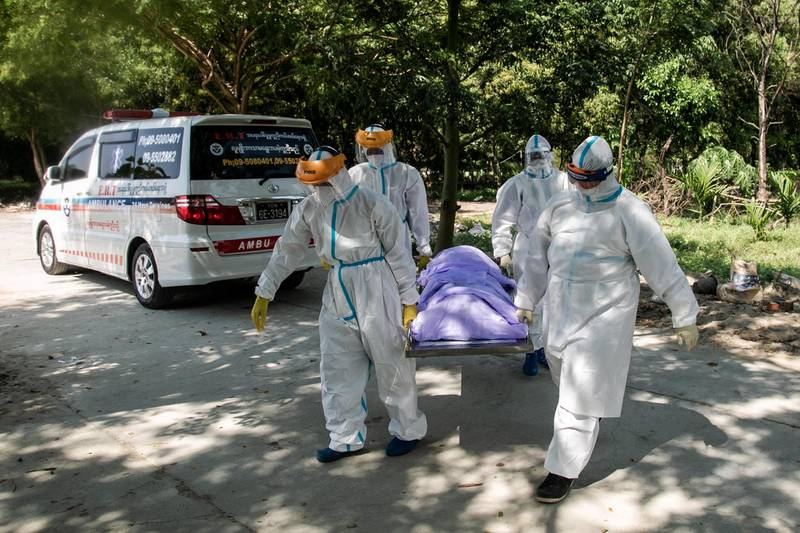 (FILES) In this file photo taken on November 25, 2020, volunteers wearing personal protective equipment (PPE) carry the body of a person suspected of dying from the Covid-19 coronavirus for their burial in the Hteinbin Muslim Cemetery in Yangon. - Living in a cemetery and isolated from his family, volunteer Sithu Aung lays another coronavirus victim to rest -- offering a crucial funeral rite to his Muslim community in Myanmar's virus-ravaged commercial capital. (Photo by Sai Aung Main / AFP) / TO GO WITH Myanmar-health-virus-religion-Islam by Lapyae KO