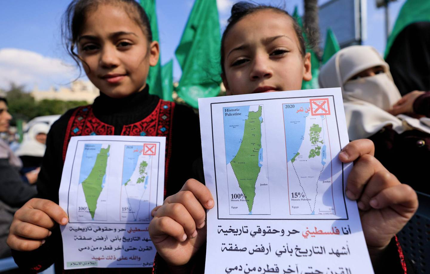Young Palestinian girls hold petitions with a map of British mandate Palestine (L) and a current map of the Palestinian territories without Israeli-annexed areas and settlements, as they take part in a demonstration by women supporters of the Hamas movement against the US President Donald Trump plan for Middle East, in Gaza City on February 5, 2020. / AFP / Emmanuel DUNAND