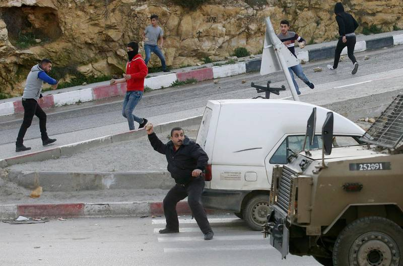 Palestinians throw stones at Israeli army vehicles after forces entered the village of Halhoul in the occupied West Bank on February 07, 2018. A Palestinian stabbed a security guard at the entrance to an Israeli settlement and was shot dead in the latest violence in the occupied West Bank, Israel's military said. / AFP PHOTO / HAZEM BADER