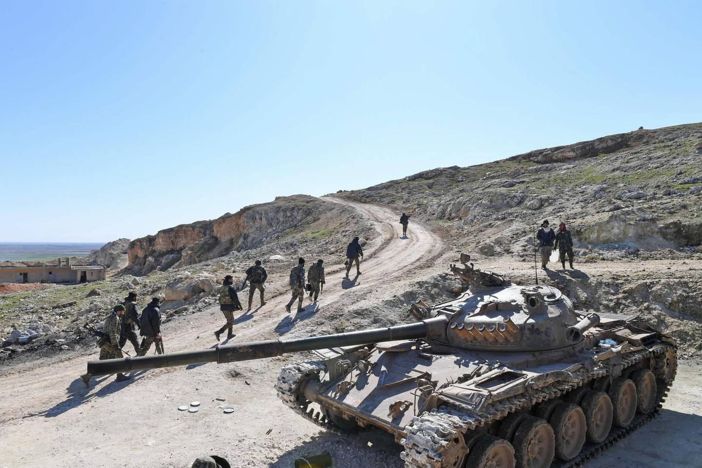 Syrian army units advance in the town of al-Eis in south Aleppo province on February 9, 2020, following battles with rebels and jihadists. Al-Eis, which overlooks the M5, was on a front that saw fierce fighting between the regime and its opponents in 2016. Syrian troops advancing north of Idlib linked up near Al-Eis with their comrades pushing south of Aleppo on Saturday, state news agency SANA said. The two units had recently waged separate battles in rural Aleppo and southern Idlib, but are now conjoined for the first time as they push north along the M5 highway.  / AFP / -