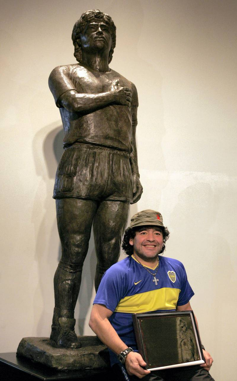 Former soccer star Diego Maradona poses in front of his statue, commissioned as a tribute by a group of fans, at the Boca Juniors Museum (Museo de la Pasion Boquense), in La Bombonera stadium, Buenos Aires, November 26th 2006. The sculpture is 2.2 meters tall and weighs some 300 kilos.  AFP PHOTO/Juan MABROMATA (Photo by JUAN MABROMATA / AFP)