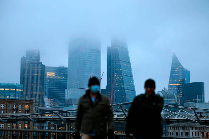 Pedestrians walk on the south bank as the mist covers buildings in the City of London on the bank holiday, December 28, 2020, as Londoners continue to live under Tier 4 lockdown restrictions. Business breathed a sigh of relief this week after a post-Brexit trade deal was agreed, but many issues remain unresolved, notably the place of financial services, which represent 80 per cent of the British economy, as the newly inked deal focuses on trade in goods. / AFP / Tolga Akmen