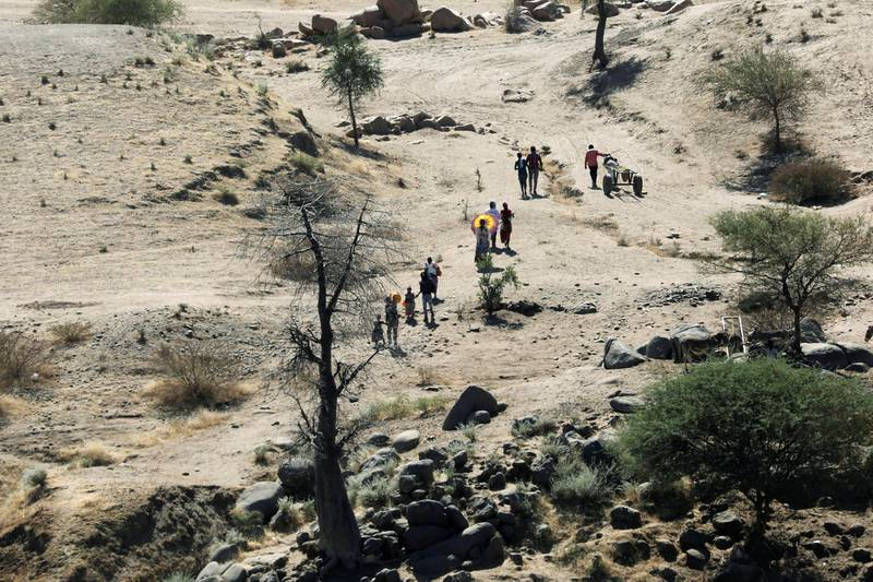 FILE PHOTO: Ethiopians fleeing from the Tigray region walk towards a river to cross from Ethiopia to Sudan, near the Hamdeyat refugee transit camp, which houses refugees fleeing the fighting in the Tigray region, on the border in Sudan, December 1, 2020. REUTERS/Baz Ratner/File Photo