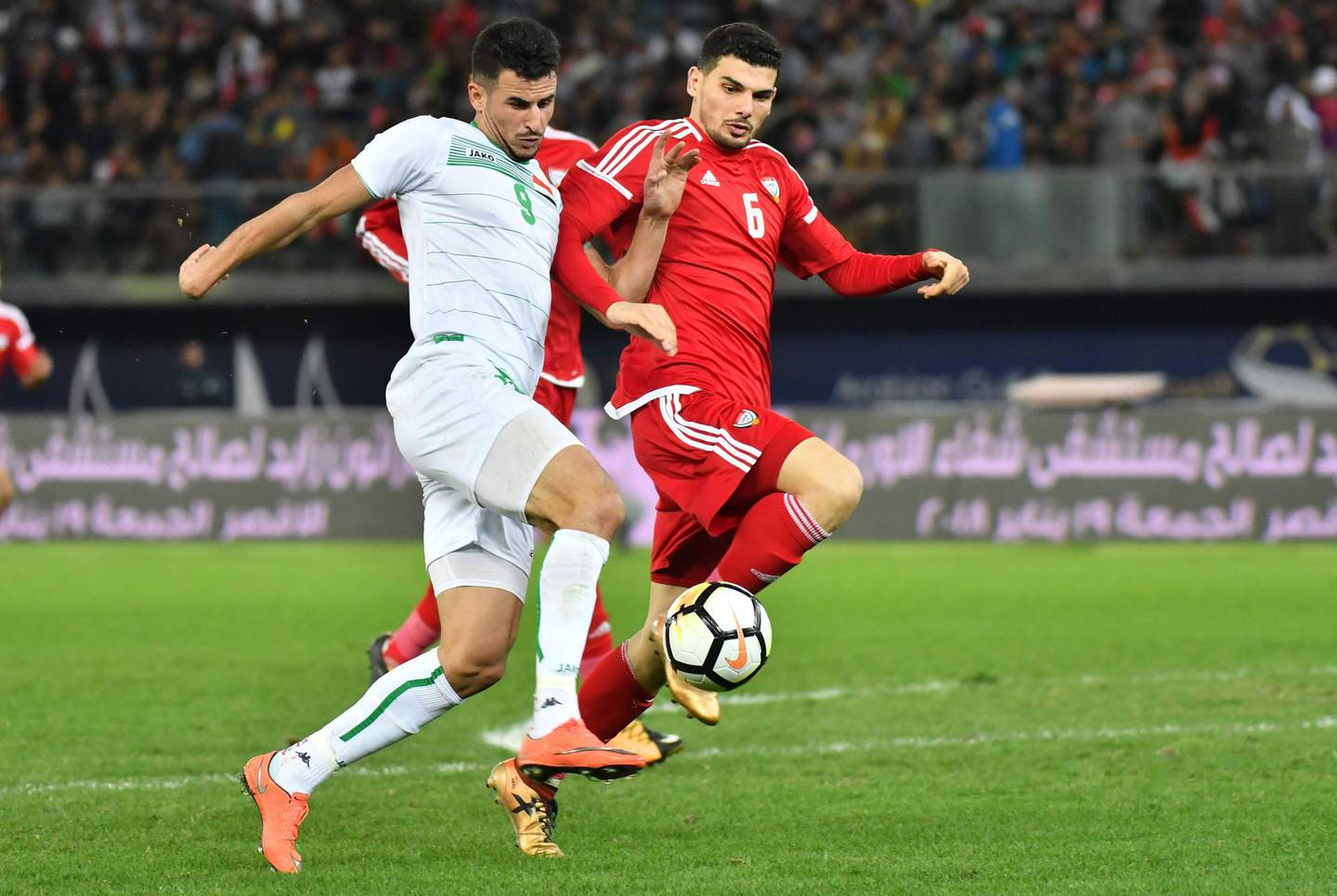 UAE's Mohanad Salem (R) fights for the ball against Iraq's Aymen Hussein during the 2017 Gulf Cup of Nations semi-final football match between Iraq and UAE at the Sheikh Jaber al-Ahmad Stadium in Kuwait City on January 2, 2018.  / AFP PHOTO / GIUSEPPE CACACE