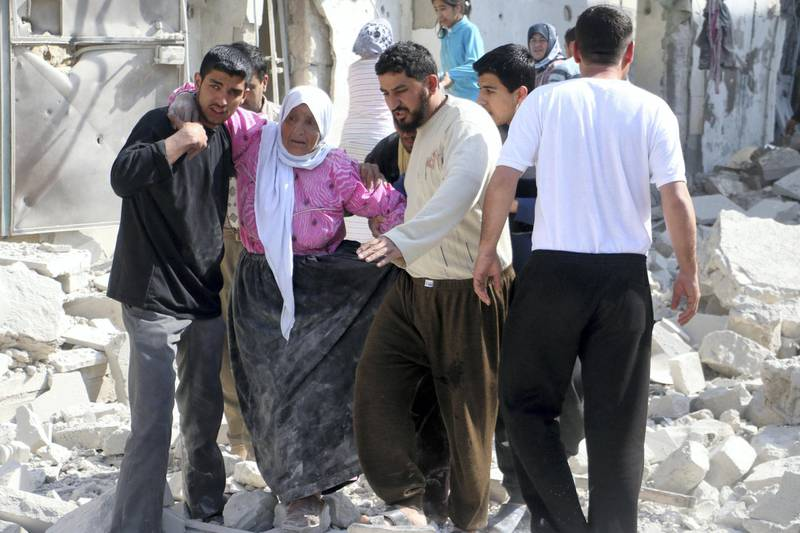 A woman is assisted to walk through the rubble of buildings following a reported air strike by Syrian government forces in the al-Sakhour district of the northern city of Aleppo on April 4, 2014. More than 150,000 people have been killed in Syria since the conflict began in March 2011, a monitoring group said in a new toll released on April 1, 2014.  AFP PHOTO / ALEPPO MEDIA CENTRE / FADI AL-HALABI (Photo by Fadi al-Halabi / AFP)