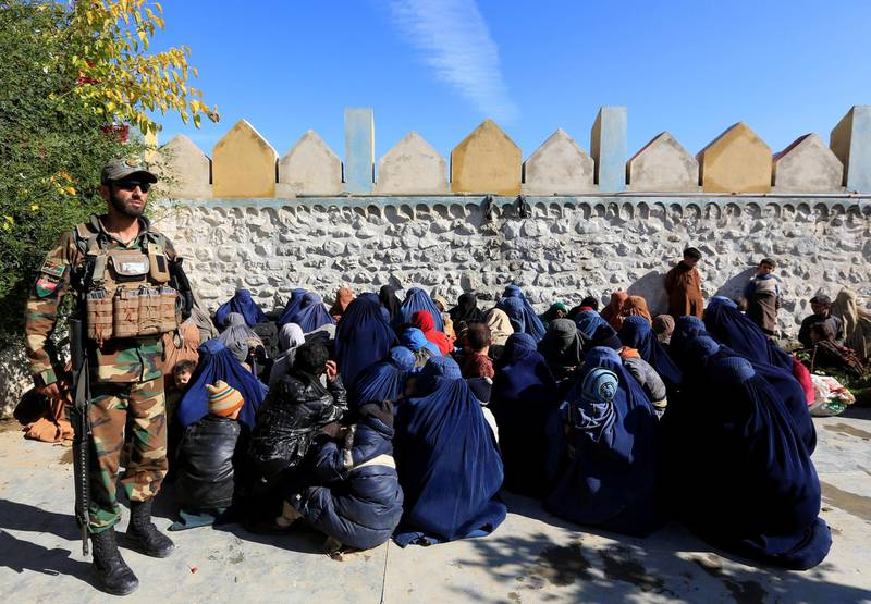 A member of the Afghan security forces watches next to family members of ISIS militants who surrendered to the Afghan government in Achin district of Nangarhar province, Afghanistan November 17, 2019. REUTERS/Parwiz