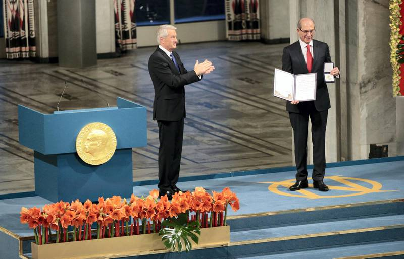 The Chairman of the Norwegian Nobel Committee Thorbjoern Jagland (L) applauds after awarding Ahmet Uzumcu (R), Director General of the Organisation for the Prohibiton of Chemical Weapons (OPCW), the 2013 Peace Nobel Prize at the Oslo City Hall on December 10, 2013. The Organisation for the Prohibiton of Chemical Weapons (OPCW) received the 2013 Peace Nobel Prize, attributed for its extensive efforts to eliminate chemical weapons.   AFP PHOTO / DANIEL SANNUM LAUTEN (Photo by DANIEL SANNUM LAUTEN / AFP)