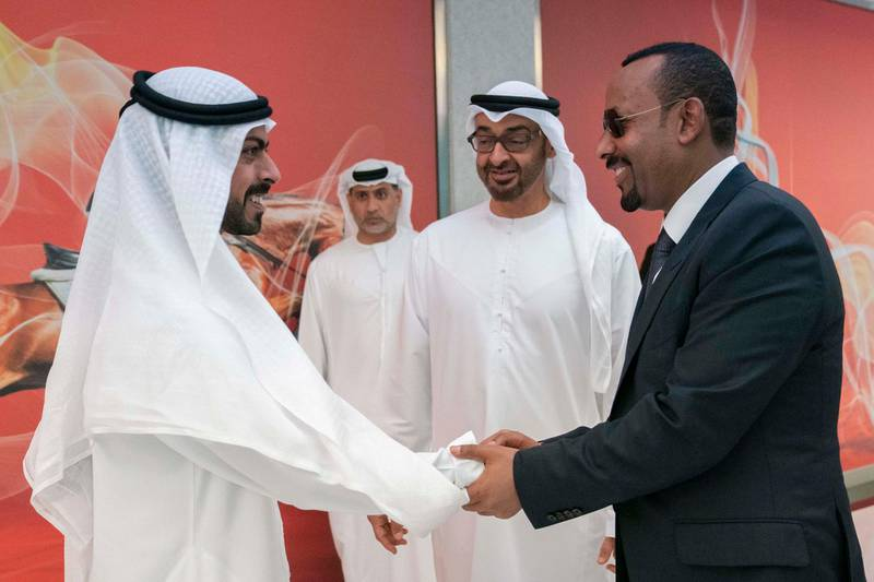 ABU DHABI, UNITED ARAB EMIRATES - March 18, 2019: HH Sheikh Khalifa bin Tahnoon bin Mohamed Al Nahyan, Director of the Martyrs' Families' Affairs Office of the Abu Dhabi Crown Prince Court (L) greets HE Abiy Ahmed, Prime Minister of Ethiopia (R), during the Special Olympics World Games Abu Dhabi 2019, at Abu Dhabi National Exhibition Centre (ADNEC). Seen with HH Sheikh Mohamed bin Zayed Al Nahyan, Crown Prince of Abu Dhabi and Deputy Supreme Commander of the UAE Armed Forces (C).  ( Ryan Carter / Ministry of Presidential Affairs )? ---