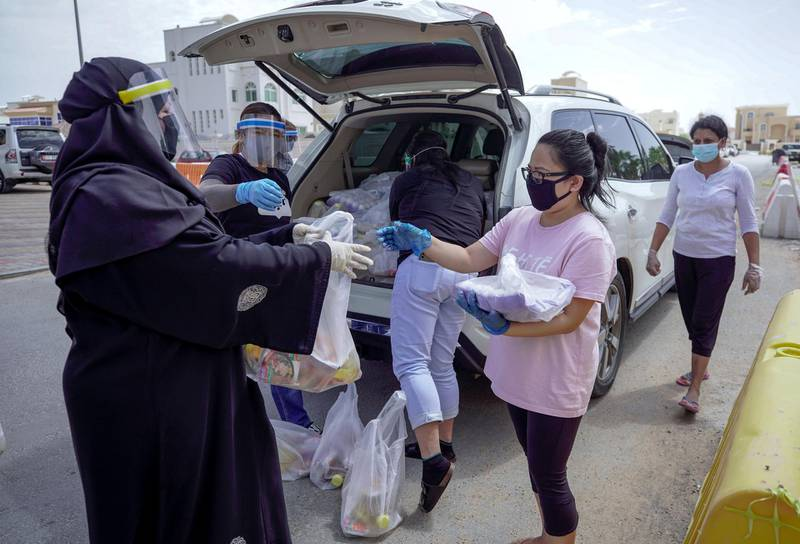 Abu Dhabi, United Arab Emirates, May 1, 2020.    Filipino-Emirati, Mona Mohamed Baraguir  (left) donates rice, eggs, cooking oil and other daily essentials to laid off workers at the Khalifa A neighborhood on a Friday morning.Victor Besa / The NationalSection:  NAReporter:  Shireena Al Nuwais