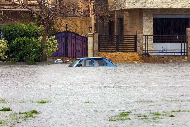 This picture taken on March 12, 2020 shows a view of an inundated car in a flooded street in  in the New Cairo suburb of the Egyptian capital amidst a heavy rain storm.  / AFP / -