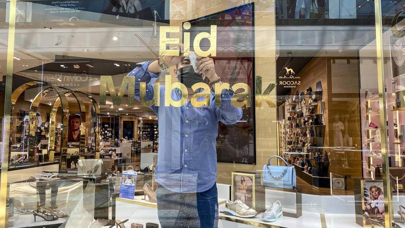 A shop attendent puts up an Eid Mubarak sticker on a shop window in the mall. Eid decorations in Festival City Mall with shoppers preparing for Eid on May 10th, 2021. Antonie Robertson / The National.Reporter: Patrick Ryan for National.
