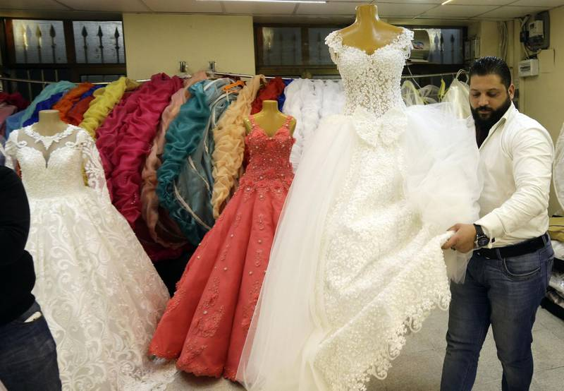 A picture taken on January 8, 2018 shows a Syrian man arranging dresses at a wedding dresses shop in the capital Damascus. For many Syrian women, aged 30 and older, who are eager to get married -- Syria's protracted conflict means potential suitors have emigrated, joined the army or lost their lives.  / AFP PHOTO / LOUAI BESHARA