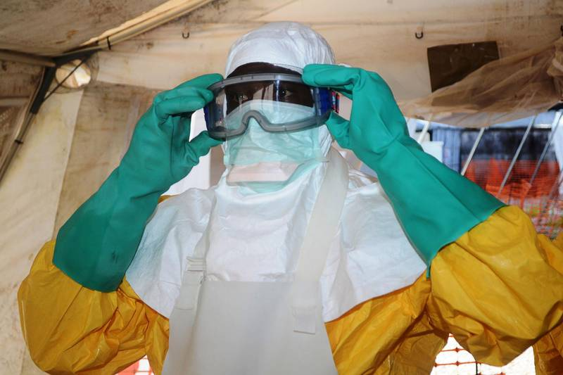 (FILES) This file photo taken on June 28, 2014 shows a member of Doctors Without Borders (MSF) putting on protective gear at the isolation ward of the Donka Hospital in Conakry, where people infected with the Ebola virus are being treated.  Four people have died of Ebola in Guinea, the first resurgence of the haemorrhagic fever in the West African nation since a 2013-2016 epidemic left thousands dead, Health Minister Remy Lamah said on February 13, 2021. / AFP / CELLOU BINANI