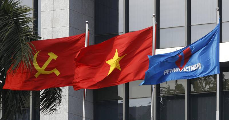 FILE PHOTO: Flag of PetroVietnam (R) flutters next to Vietnamese national flag (C) and Communist Party flag in front of the headquarters of PetroVietnam in Hanoi January 11, 2016.    REUTERS/Kham/File Photo