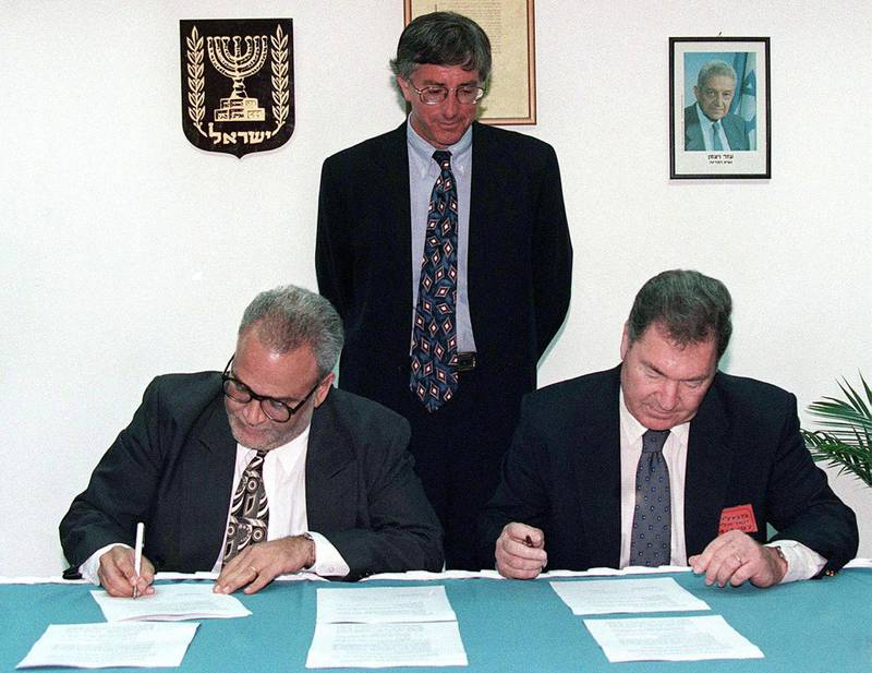 United States' special envoy Dennis Ross looks on as Saeb Erekat (L), the chief Palestinian negotiator, and Dan Shomron, the chief Israeli negotiator, initial the documents that bring to a conclusion the long-delayed and overdue Israeli troop redeployment in the West Bank city of Hebron. Palestinian President Arafat and Israeli Prime Minister Netanyahu shook hands on the deal, and now both sides will take the agreement to their respective cabinets for approval. The troop redeployment will take place within ten days.  MIDEAST