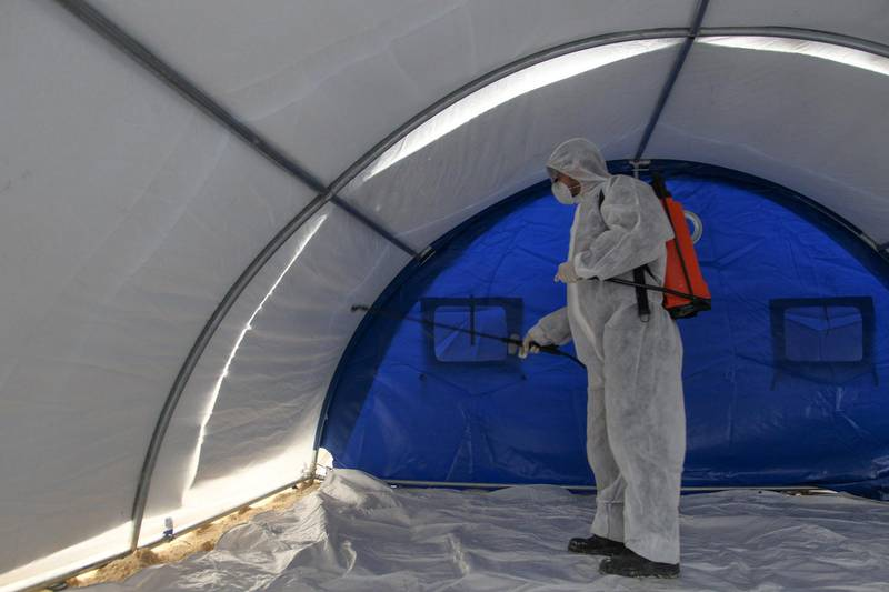 A member of the Syrian Violet NGO disinfects a triage tent erected for suspected coronavirus patients outside the Ibn Sina Hospital in Syria's northwestern Idlib city on March 19, 2020. - Syrian authorities on March 13 announced measures aimed at preventing coronavirus from reaching the war-torn country, including school closures and a ban on smoking shisha in cafes, state media reported. (Photo by Abdulaziz KETAZ / AFP)