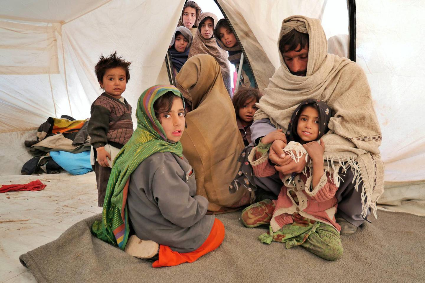 Pictured: Najibullah and his wife Khatima, who remains covered, sit in the tent that is now where they call home with their children. Other children pop their heads inside the tent to see what is going on.  Photo by Charlie Faulkner January 2021