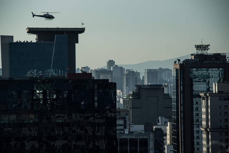 A helicopter lands on the roof of a building in downtown Sao Paulo, Brazil on June 23, 2017. Airbus' subsidiary Voom gives an alternative for those willing to avoid Sao Paulo's heavy car traffic, offering a helicopter service similar to the car service offered by Uber. Sao Paulo counts one car every two inhabitants and during rush time there are between 330 and 576 km of traffic jams.  / AFP PHOTO / NELSON ALMEIDA