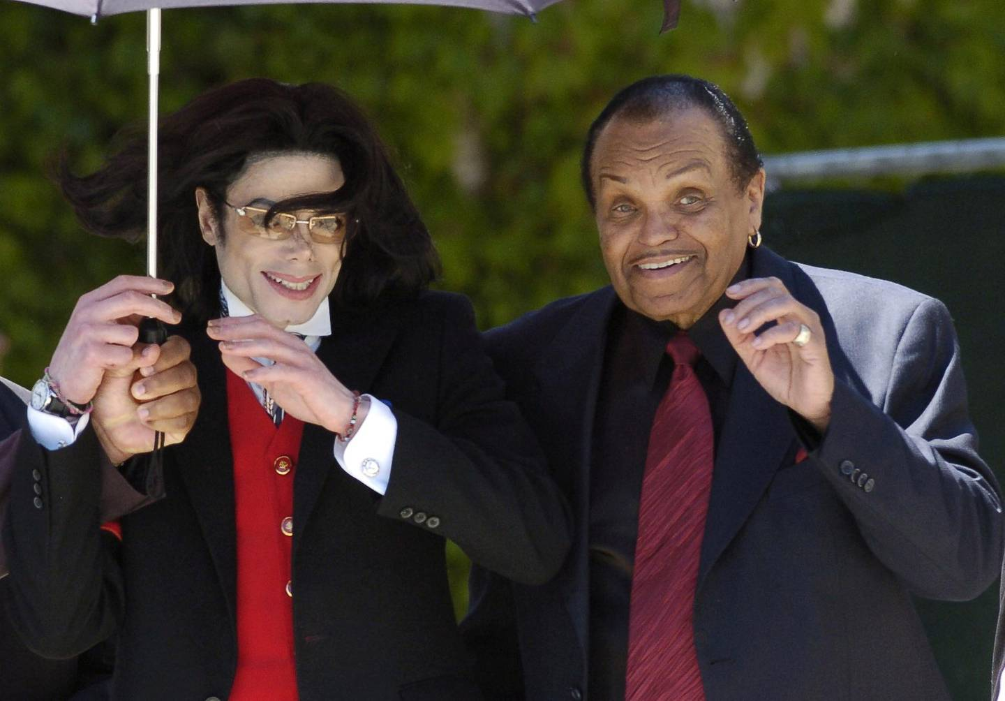 FILE PHOTO:  Pop star Michael Jackson and his father Joe Jackson gestures to his fans as he leaves the Santa Barbara county courthouse in Santa Maria, California.   REUTERS/Phil Klein/File Photo