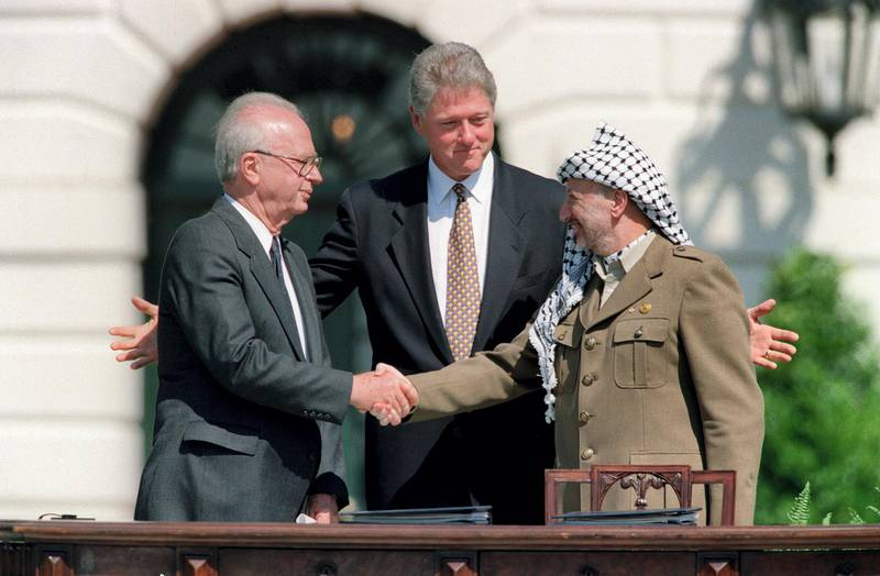 US President Bill Clinton (C) stands between PLO leader Yasser Arafat (R) and Israeli Prime Minister Yitzahk Rabin (L) as they shake hands for the first time, on September 13, 1993 at the White House in Washington DC, after signing the historic Israel-PLO Oslo Accords on Palestinian autonomy in the occupied territories. (Photo by J. DAVID AKE / AFP)