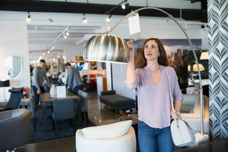 Woman checking price tag on lamp in home furnishings store. Getty Images