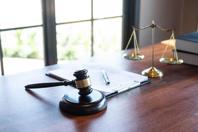 Judge gavel with Justice at law firm in background with legal case document contract, law and justice, attorney, lawsuit. Getty Images