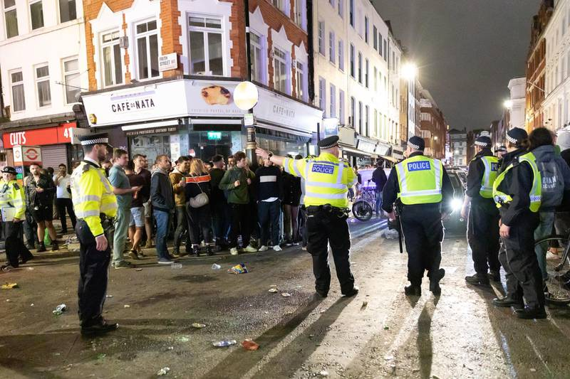 epa08528415 Police officers direct traffic as revellers drink and socialize in the street in Soho, London, Britain, 04 July 2020 (issued 05 July 2020). Pubs, restaurants, places of worship, hairdressers and other businesses have reopened their doors across the UK on 'Super Saturday' after more than three months of lockdown due to the coronavirus pandemic.  EPA/VICKIE FLORES